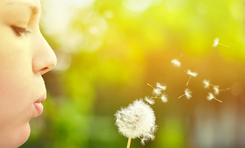 girl blowing dandelion and problems away